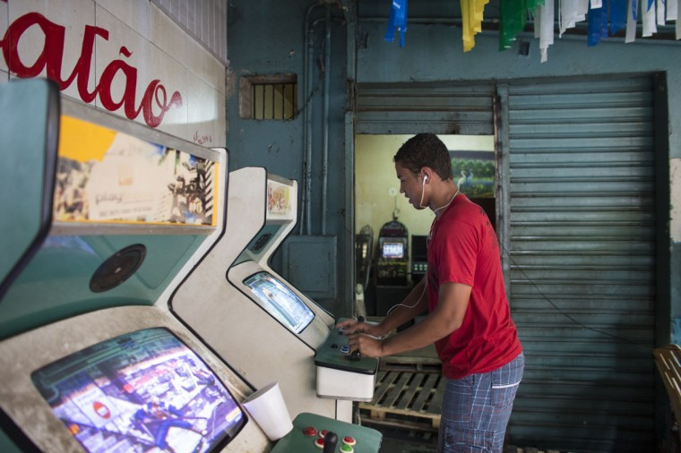A young man plays on an arcade machine in a bar near Manaus port on June 17, 2014 in Manaus, Brazil. Group D teams, England lost 2-1 to Italy in their opening match of the 2014 FIFA World Cup in Manaus on June 14, 2014. (Photo by Oli Scarff/Getty Images)