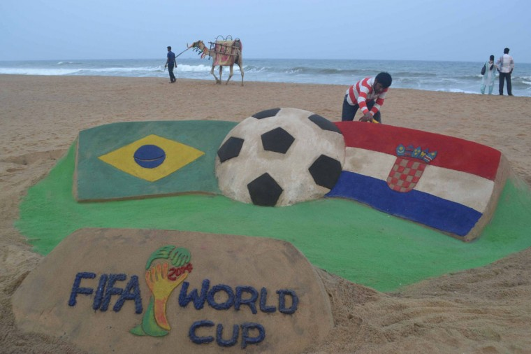Indian sand artist Sudarsan Pattnaik gives final touches on his sand sculpture ahead of the first football match of the FIFA World Cup 2014 between Brazil and Croatia, at Puri beach some 65 kilometers away from Bhubaneswar on June 11, 2014. With just days to go before the start of the FIFA World Cup 2014 in Brazil, football fans are showing their support for the event by purchasing football-related merchandise and through hairstyles and team strips. (Asit Kumar/AFP/Getty Images)