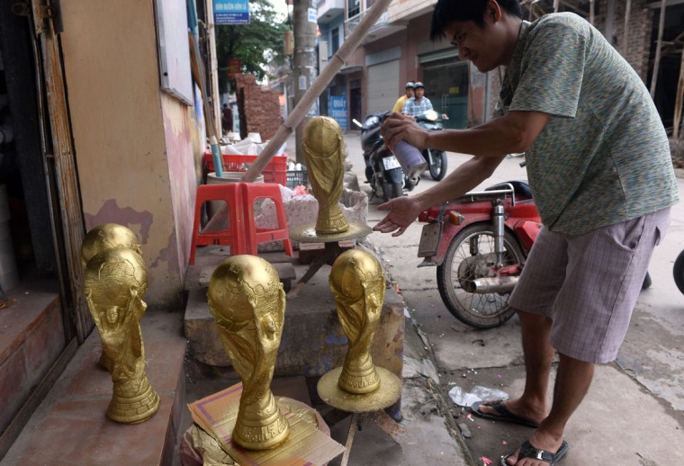 A man paints replicas of the football World Cup trophy at a shop in Bat Trang pottery village on the outskirts of Hanoi on June 12, 2014. The trophies are sold for about 3.5 US dollars to local football fans. (Hoang Dinh Nam/AFP/Getty Images)