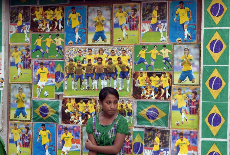 An Indian soccer fan looks on amid paraphernalia of the Brazilian soccer team ahead of their first match in the FIFA World Cup against Croatia, in Kolkata on June 12, 2014. Football fans in the eastern Indian city are gearing up for the upcoming Brazil FIFA World Cup 2014 and decorating their clubs and locality with football-related paraphernalia. (Dibyangshu Sarkar/AFP/Getty Images)