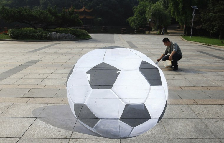 Artist He Haomin paints a 3-dimensional soccer ball at a park in Changsha, Hunan province, June 12, 2014. Picture taken June 12, 2014. (China Daily/Reuters)