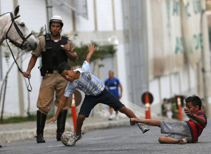 Kids play soccer on a street as a police officer watches outside Independencia stadium before the start of the Argentine national team training session in preparation for 2014 World Cup in Belo Horizonte, June 11, 2014. (Leonhard Foeger/Reuters)