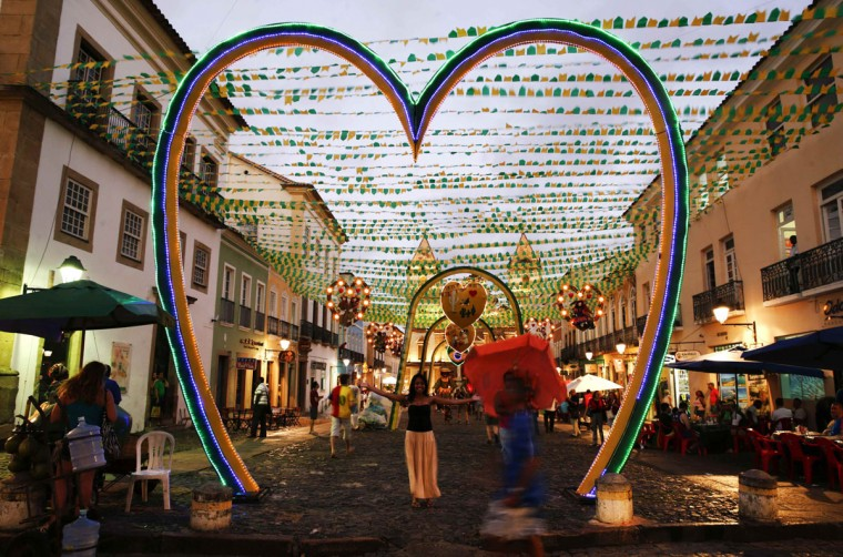 A woman pose for a picture under street decorations on the public square where the fan zone for soccer matches will be held at Pelourinho neigborhood ahead of the 2014 World Cup in Salvador June 11, 2014. (Marcos Brindicci/Reuters)