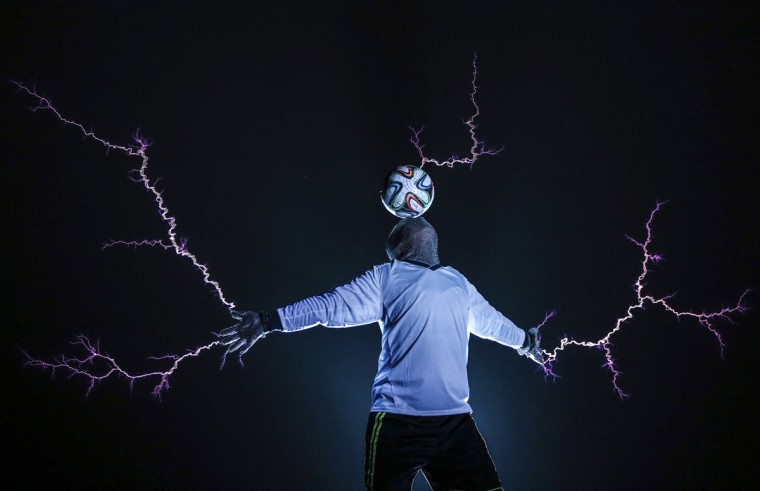 A member of the Thunderbolt Craziness band wearing a metal suit balances a soccer ball on his head as electricity is discharged from Tesla coils during a performance to celebrate the 2014 Brazil World Cup, in Changle, Fujian province June 12, 2014. The band specialises in producing electric arcs from Tesla coils that have been charged with one million volts of electricity. Picture taken June 12, 2014. (Stringer/Reuters)