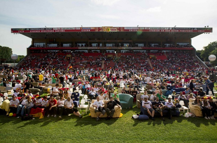 "People watch Germany playing against Portugal in a World Cup soccer match during a public viewing event at the Alte Foersterei stadium in Berlin, June 16, 2014. Berlin's Union Berlin soccer team, which plays in the second division, has turned its stadium into a vast ""World Cup living room,"" allowing fans to transport their own sofa onto the pitch to watch the games for free. At least 12,000 people are expected to watch Germany's first World Cup game against Portugal on Monday, on up to 850 couches. (Thomas Peter/Reuters)"