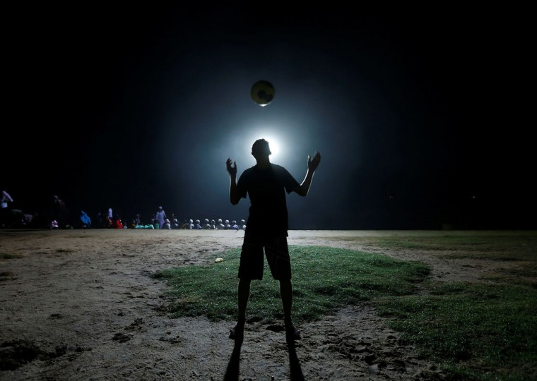 A boy is silhouetted as he plays with a soccer ball at night in Colombo June 11, 2014. The 2014 FIFA soccer World Cup will be held in Brazil from June 12 through July 13. (Dinuka Liyanawatte/Reuters)