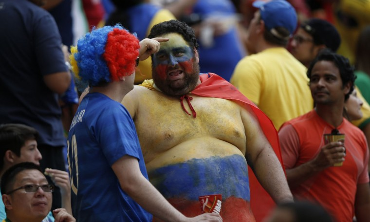 A Colombian fan chats with a fellow supporter during the Group C football match between Colombia and Ivory Coast at the Mane Garrincha National Stadium in Brasilia during the 2014 FIFA World Cup on June 19, 2014. (Adrian Dennis/AFP/Getty Images)