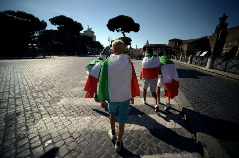 Italy's fans walk in Rome, on their way to watch the FIFA World Cup 2014 football match Italy vs Costa Rica displayed on a giant screen in central Rome's Piazza Venezia on June 20, 2014. (Filippo Monteforte/AFP/Getty Images)