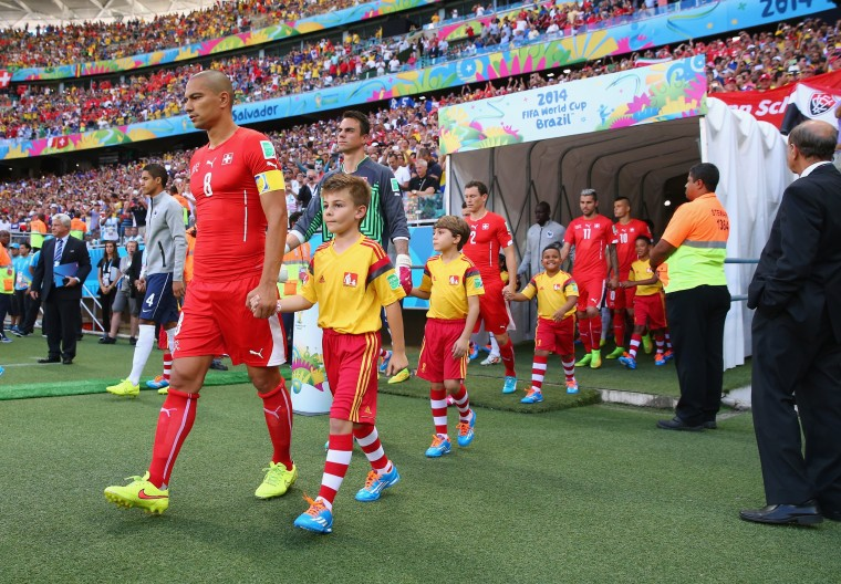 Gokhan Inler of Switzerland leads his team to the field with their player escorts during the 2014 FIFA World Cup Brazil Group E match between Switzerland and France at Arena Fonte Nova on June 20, 2014 in Salvador, Brazil. (Photo by Elsa/Getty Images)