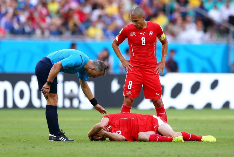 Steve von Bergen of Switzerland lies on the pitch as referee Bjorn Kuipers stands over during the 2014 FIFA World Cup Brazil Group E match between Switzerland and France at Arena Fonte Nova on June 20, 2014 in Salvador, Brazil. (Photo by Elsa/Getty Images)