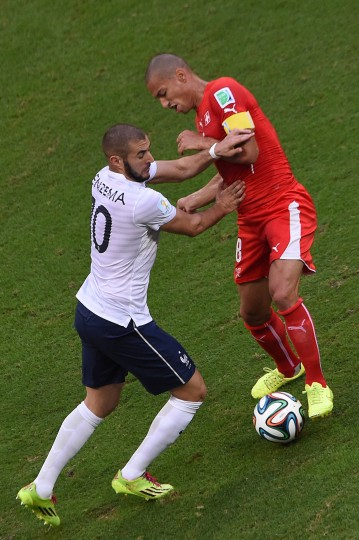 Switzerland's midfielder Goekhan Inler (R) vies with France's forward Karim Benzema (L) during a Group E football match between Switzerland and France at the Fonte Nova Arena in Salvador during the 2014 FIFA World Cup on June 20, 2014. (Dimitar Dilkoff/AFP/Getty Images)