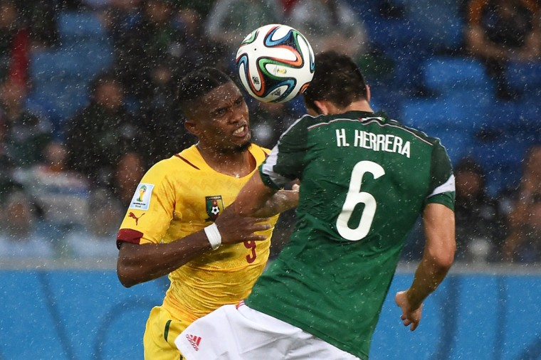 Cameroon's forward and captain Samuel Eto'o (L) fights for the ball with Mexico's midfielder Hector Herrera during a Group A football match between Mexico and Cameroon at the Dunas Arena in Natal during the 2014 FIFA World Cup on June 13, 2014. (Christophe Simon/AFP/Getty Images)