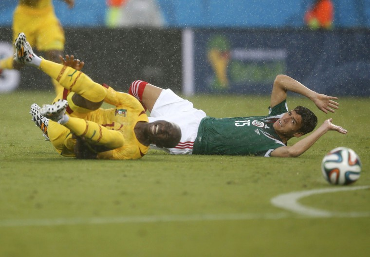 Cameroon's Stephane Mbia (L) and Mexico's Hector Moreno lie on the ground as they fight for the ball during their 2014 World Cup Group A soccer match at the Dunas arena in Natal June 13, 2014. (Toru Hanai/Reuters)