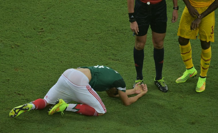 Mexico's midfielder Hector Herrera reacts after falling during the Group A football match between Mexico and Cameroon at the Dunas Arena in Natal during the 2014 FIFA World Cup on June 13, 2014. (Gabriel Bouys/AFP/Getty Images)