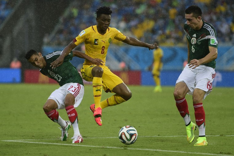 Cameroon's forward Benjamin Moukandjo (C) fights for the ball with Mexico's midfielder Jose Juan Vazquez and Mexico's midfielder Hector Herrera (R) during a Group A football match between Mexico and Cameroon at the Dunas Arena in Natal during the 2014 FIFA World Cup on June 13, 2014. (Pierre-Philippe Marcou/AFP/Getty Images)