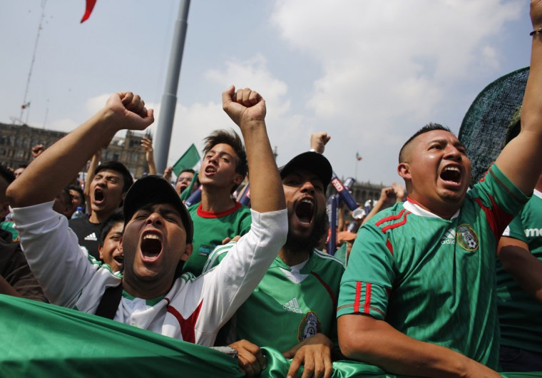 Mexican soccer fans react while watching the 2014 World Cup soccer match between Mexico and Cameroon as it was broadcasted on a large screen at Zocalo square in downtown Mexico City, June 13, 2014. (Tomas Bravo/Reuters)