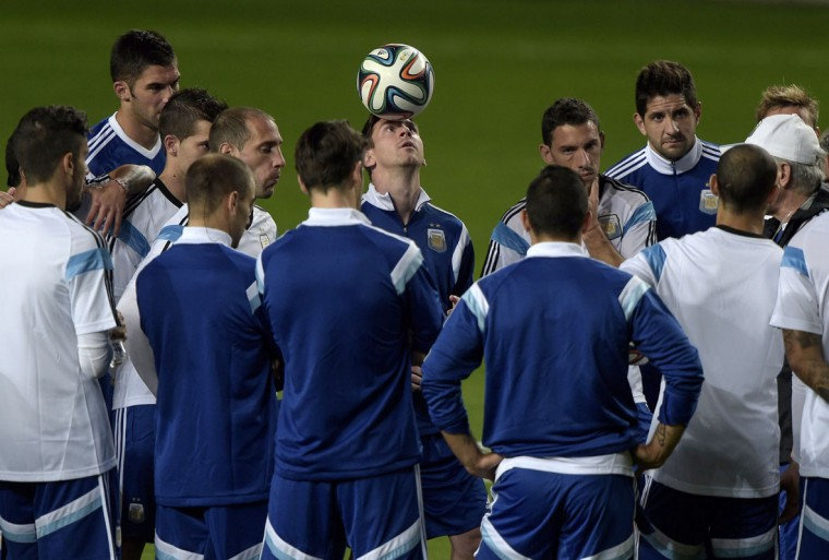 Argentina's forward Lionel Messi (C) controls the ball on his head while coach Alejandro Sabella (R) talks to his players during a training session at the Independencia Arena, in Belo Horizonte ahead of a 2014 FIFA World Cup Brazil Group F football match against Bosnia and Hercegovina to be held at the Maracana Stadium in Rio de Janeiro on June 15. AFP PHOTO / (Juan Mabromata/AFP/Getty Images)