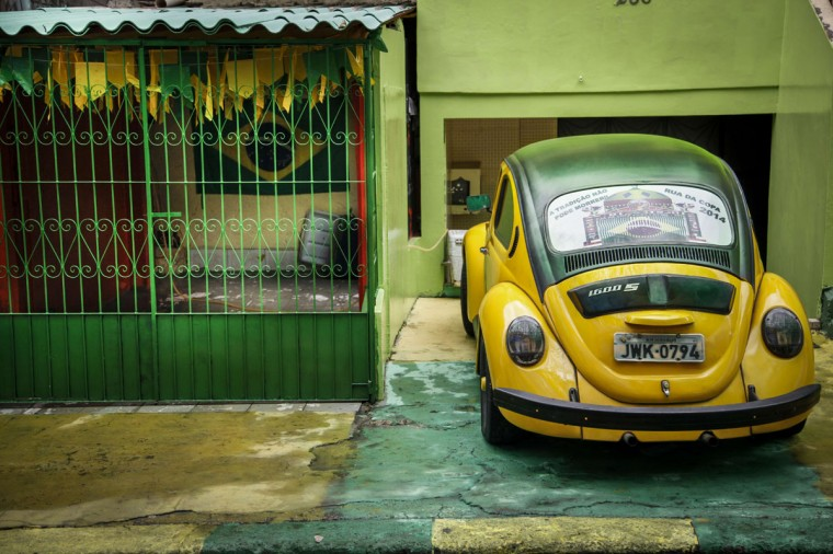 """A beetle volkswagen, locally known as """"fusca"""", painted in the green-yellow Brazilian national colours, is parked at the Praca 14 de Janeiro neighborhood in Manaus, one of the host cities of Fifa World Cup 2014, Amazonas state, Brazil, on June 11, 2014. (Raphael Alves/AFP/Getty Images)"""