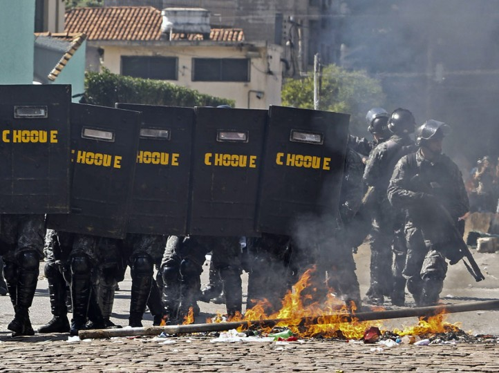 "Riot policemen move by a fire set up by demonstrators during an anti-World Cup protest on the morning the Brazilian mega-city hosts the tournament's opening match, in Sao Paulo on June 12, 2014. Police fired tear gas, stun grenades and rubber bullets to break up dozens of protesters gathering near a Sao Paulo subway station with a red banner reading ""If we have no rights, there won't be a Cup,"" saying they planned to march as close as possible to Corinthians Arena, the city's World Cup stadium. (Miguel Schincariol/AFP/Getty Images)"