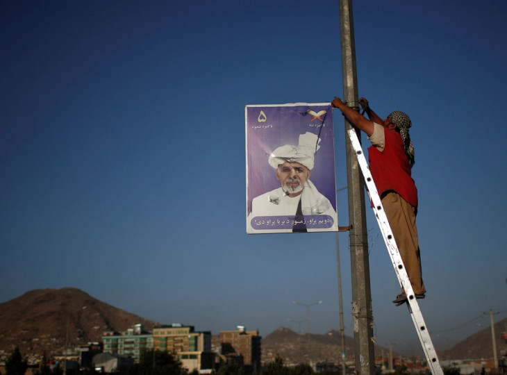 A man removes a poster of Afghan presidential candidate Ashraf Ghani Ahmadzai a day after election campaigns officially ends in Kabul June 12, 2014. The second round of Afghanistan's presidential election will take place on June 14. (Ahmad Masood/Reuters)