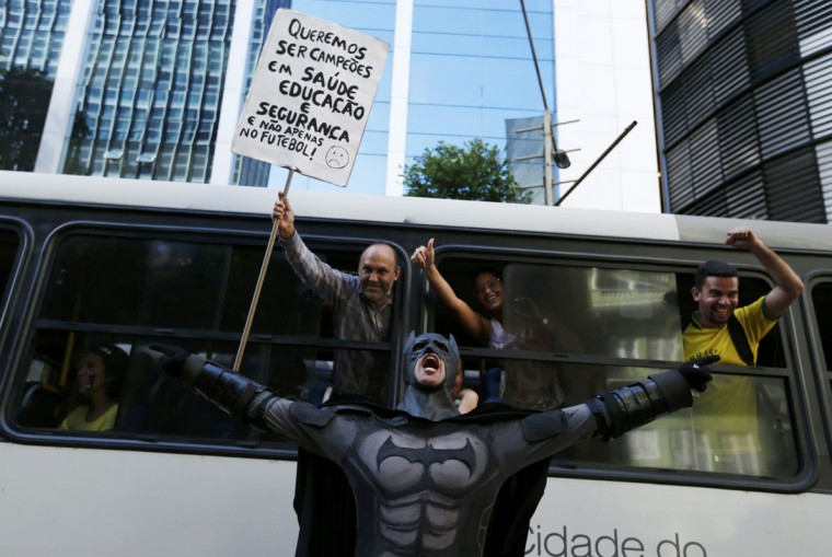 """An anti-government demonstrator dressed as Batman yells slogans accompanied by passengers on a bus, during a protest against the 2014 World Cup in Rio de Janeiro June 12, 2014. Placard reads """"We want to be the champions in healthcare, education and not just in football."""" (Pilar Olivares/Reuters)"""