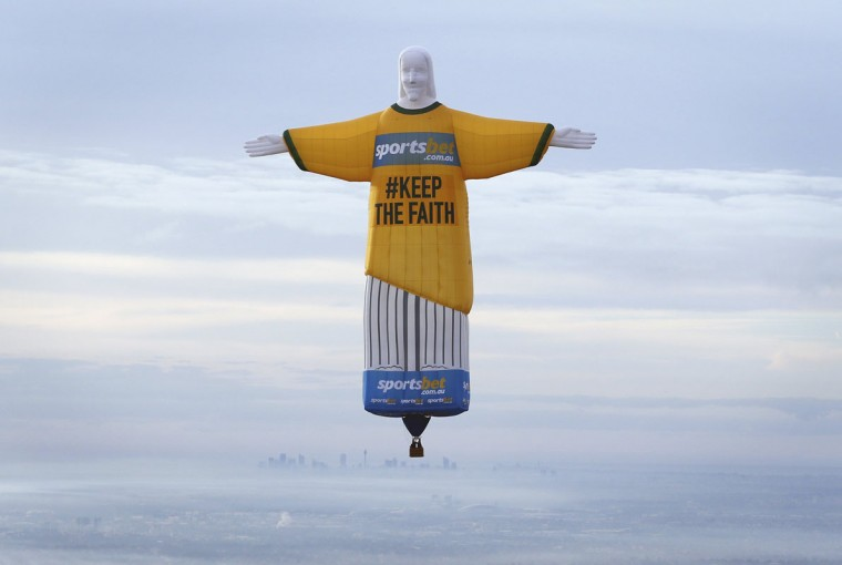 """A hot air balloon in the shape of Brazil's Christ the Redeemer statue flies over the Sydney skyline June 12, 2014. The balloon, measuring over 45 metres tall and built in Britain, flew over the Sydney skyline on Thursday to publicise an online sports betting agency, asking fans of Australia's national soccer team """"Socceroos"""" to 'keep the faith' as they compete in the 2014 World Cup in Brazil. (David Callow/Handout via Reuters)"""