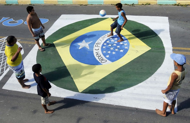 Kids juggle with a ball on a street painted with a Brazilian flag in Mangaratiba June 12, 2014. (Alessandro Garofalo/Reuters)