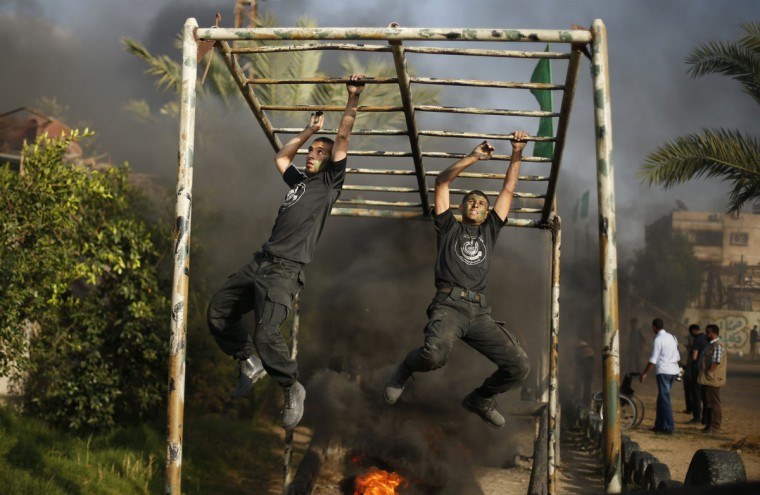 Young Palestinians climb across a bar over fire during a military-style exercise at a summer camp organized by the Hamas movement in Gaza City June 12, 2014. Hamas stages dozens of military-style summer camps for young Palestinians in the Gaza strip to prepare them to confront any possible Israeli attack, organisers said. (Suhaib Salem/Reuters)