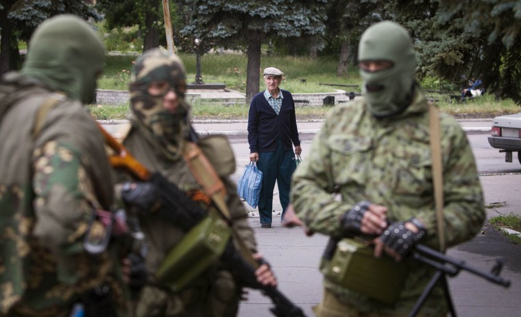 A man looks at armed pro-Russian separatists at a town center in Snizhnye in eastern Ukraine June 12, 2014. (Shamil Zhumatov/Reuters)