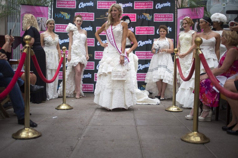 """Designer and model Susan Brennan of Orchard Lake, Michigan presents her dress named """"Romance on a Roll"""" after taking first prize at the 10th annual toilet paper wedding dress contest in Midtown, New York June 12, 2014. The materials to make the dress include 20 rolls of Charmin Ultra Soft, white and clear tape, Elmer's glue and thread. There was something old, something new, something borrowed and something double-ply for 10 designers who battled it out on Thursday for $10,000 and the top prize in the 10th annual toilet paper wedding dress contest held in New York City. (Adrees Latif /Reuters)"""