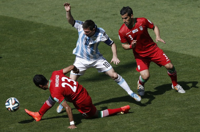 Iran's defender Mehrdad Pooladi (L), Argentina's defender Hugo Campagnaro (R) and Argentina's forward and captain Lionel Messi vie during the Group F football match between Argentina and Iran at the Mineirao Stadium in Belo Horizonte during the 2014 FIFA World Cup in Brazil on June 21, 2014. (Adrian Dennis/AFP/Getty Images)