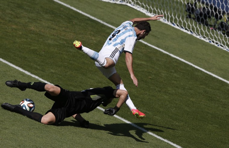Argentina's forward Gonzalo Higuain (top) and Iran's goalkeeper Alireza Haqiqi vie during the Group F football match between Argentina and Iran at the Mineirao Stadium in Belo Horizonte during the 2014 FIFA World Cup in Brazil on June 21, 2014. (ADrian Dennis/AFP/Getty Images)