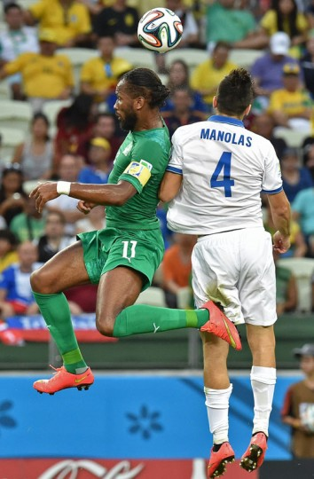 Ivory Coast's forward and captain Didier Drogba (L) fights for the ball with Greece's defender Koastas Manolas during a Group C football match between Greece and Ivory Coast at the Castelao Stadium in Fortaleza during the 2014 FIFA World Cup on June 24, 2014. (Issouf Sanogo/AFP/Getty Images)