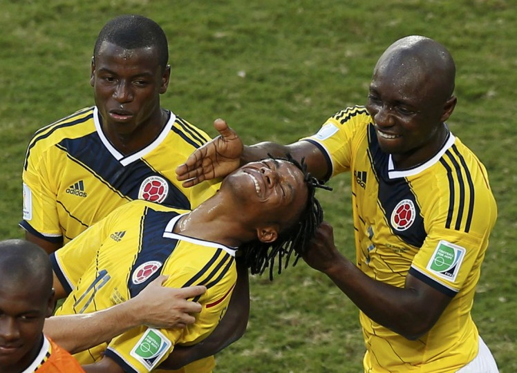 Colombia's Juan Cuadrado (C) is congratulated by his teammates Adrian Ramos (L) and Pablo Armero (R) after he scored a goal from a penalty kick during their 2014 World Cup Group C soccer match against Colombia at the Pantanal arena in Cuiaba June 24, 2014. (Suhaib Salem/Reuters)