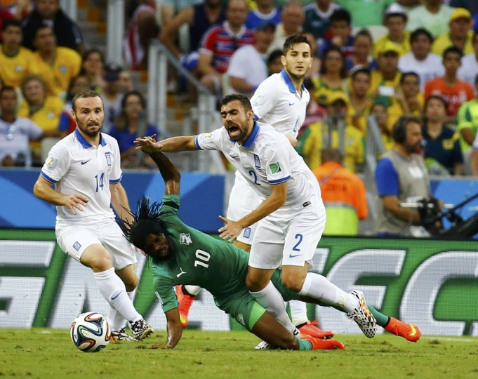 Ivory Coast's Gervinho falls while fighting for the ball with Greece's Giannis Maniatis (R) during their 2014 World Cup Group C soccer match at the Castelao arena in Fortaleza June 24, 2014. (Marcelo Del Pozo/Reuters)
