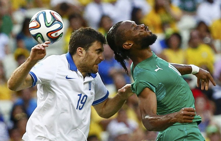 Greece's Sokratis Papastathopoulos (L) fights for the ball with Ivory Coast's Didier Drogba during their 2014 World Cup Group C soccer match at the Castelao arena in Fortaleza June 24, 2014. (Paul Hanna/Reuters)