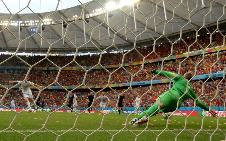 Spain's midfielder Xabi Alonso (L) scores a penalty during a Group B football match between Spain and the Netherlands at the Fonte Nova Arena in Salvador during the 2014 FIFA World Cup on June 13, 2014. (Damien Meyer/AFP/Getty Images)