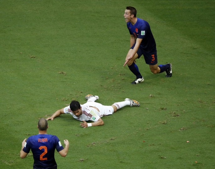 Spain's Diego Costa lies on the pitch after being fouled by Stefan de Vrij of the Netherlands (R) during their 2014 World Cup Group B soccer match at the Fonte Nova arena in Salvador June 13, 2014. (Fabrizio Bensch/Reuters)