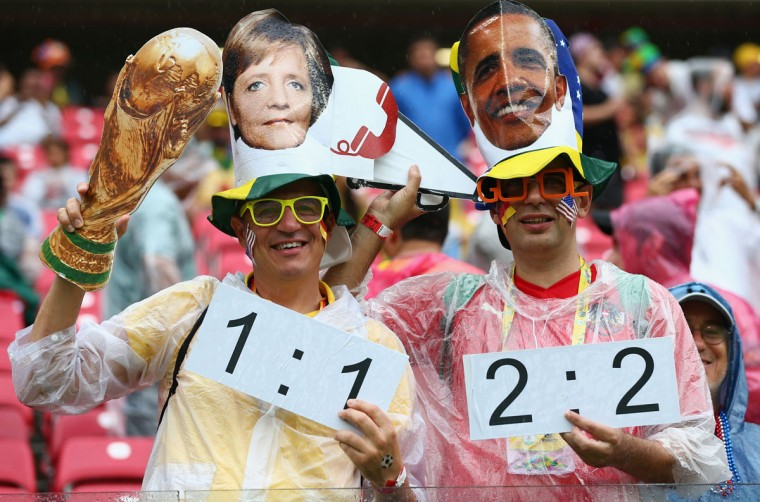Fans hold up a replica of the World Cup trophy while wearing masks of Angela Merkel and Barack Obama during the 2014 FIFA World Cup Brazil group G match between the United States and Germany at Arena Pernambuco on June 26, 2014 in Recife, Brazil. (Photo by Robert Cianflone/Getty Images)