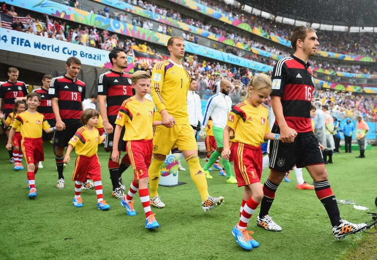 Philipp Lahm of Germany leads his team to the field with their player escorts prior to the 2014 FIFA World Cup Brazil group G match between the United States and Germany at Arena Pernambuco on June 26, 2014 in Recife, Brazil. (Photo by Jamie McDonald/Getty Images)