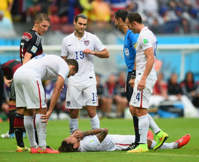 Jermaine Jones of the United States lies on the field and is checked on by teammates Clint Dempsey (2nd L), Graham Zusi (3rd L) and Brad Davis (R) as Bastian Schweinsteiger of Germany and referee Ravshan Irmatov look on during the 2014 FIFA World Cup Brazil group G match between the United States and Germany at Arena Pernambuco on June 26, 2014 in Recife, Brazil. (Photo by Jamie McDonald/Getty Images)