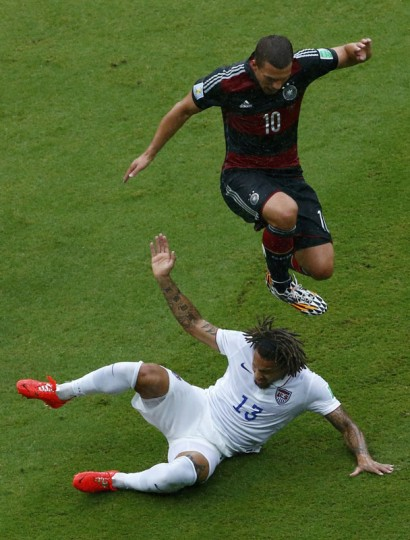 Germany's Lukas Podolski jumps over Jermaine Jones of the U.S. during their 2014 World Cup Group G soccer match at the Pernambuco arena in Recife June 26, 2014. (Ruben Sprich/Reuters)