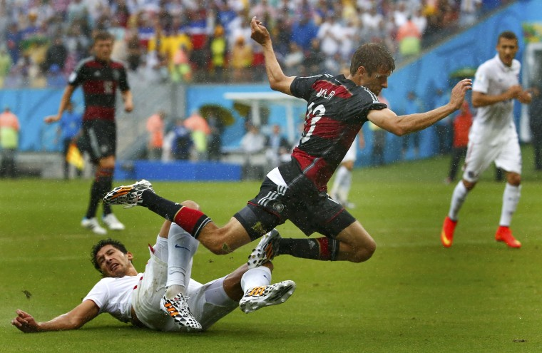 Omar Gonzalez of the U.S. (in white) takles Germany's Thomas Mueller (R) during their 2014 World Cup Group G soccer match at the Pernambuco arena in Recife June 26, 2014. (Tony Gentile/Reuters)