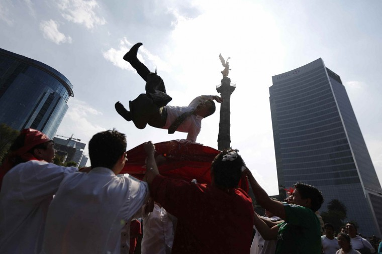 Mexican soccer fans throw a man in the air as they celebrate the 0-0 draw between Mexico and Brazil in their 2014 World Cup soccer match, at the Angel of Independence monument, in Mexico City June 17, 2014. (Bernardo Montoya/Reuters)