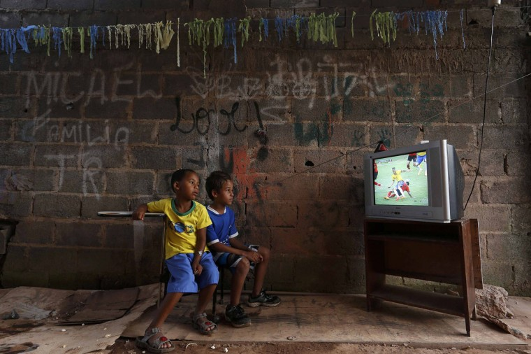 Boys watch a screening of the 2014 World Cup Group A soccer match between Brazil and Mexico, at the slum of Varjao on the outskirts of Brasilia June 17, 2014. (Ueslei Marcelino/Reuters)