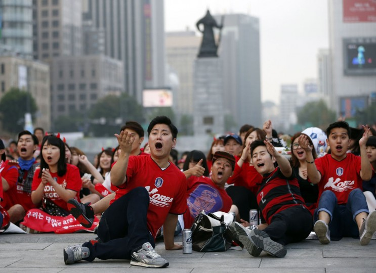 Soccer fans of South Korea react as they watch a live television broadcast of their 2014 World Cup Group H soccer match against Belgium, in Seoul June 27, 2014. Jan Vertonghen's late goal saw 10-man Belgium beat South Korea 1-0 in their final Group H match on Thursday, despite having Steven Defour sent off just before halftime for a nasty two-footed challenge. (Kim Hong-Ji/Reuters)