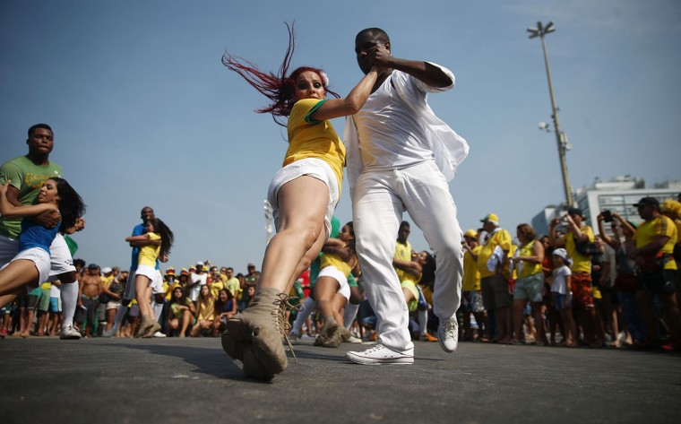 Members from the group Cia Dom, based in the Cantagalo favela, perform in Copacabana ahead of Brazil's match on June 28, 2014 in Rio de Janeiro, Brazil. Brazil plays Chile today in the knockout stage of the 2014 FIFA World Cup. (Photo by Mario Tama/Getty Images)