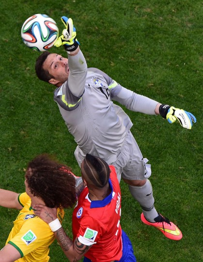 Brazil's goalkeeper Julio Cesar (R) punches the ball away as Brazil's defender David Luiz (L) challenges Chile's midfielder Arturo Vidal during the round of 16 football match between Brazil and Chile at The Mineirao Stadium in Belo Horizonte during the 2014 FIFA World Cup on June 28, 2014. (Francois Xavier Marit/AFP/Getty Images)