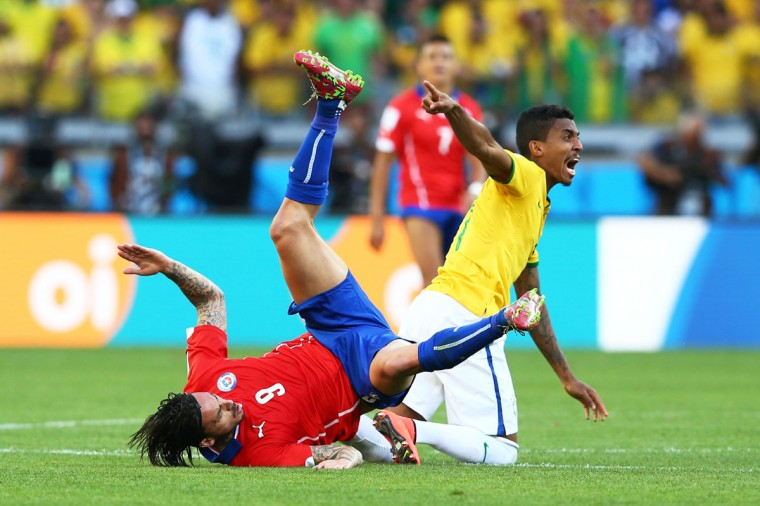 Mauricio Pinilla of Chile falls as Luiz Gustavo of Brazil reacts during the 2014 FIFA World Cup Brazil round of 16 match between Brazil and Chile at Estadio Mineirao on June 28, 2014 in Belo Horizonte, Brazil. (Photo by Quinn Rooney/Getty Images)