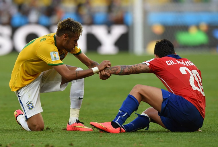 Brazil's forward Neymar (L) prepares to stand up with Chile's midfielder Charles Aranguiz during the round of 16 football match between Brazil and Chile at The Mineirao Stadium in Belo Horizonte during the 2014 FIFA World Cup on June 28, 2014. (Vanderlei ALmeida/AFP/Getty Images)